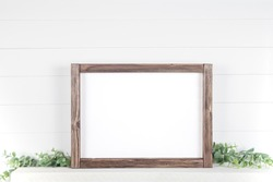 Mock up A4 horizontal frame made of rough wood with on a shelf with greens on a white background