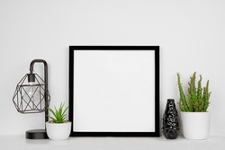 Mock up black square frame with home decor and potted plants. White shelf and wall. Copy space.