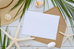 Mock up card template on white wooden background. Tropical palm leaf, summer hat, seastars and craft envelope. Invitation or greeting card concept