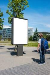 Mock up. Child looking at vertical blank billboard outdoors, outdoor advertising, public information board in the street.