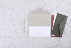Mock up concept with wedding Invitation, envelopes, cards papers on white background with pen and decoration. Top view, flat lay