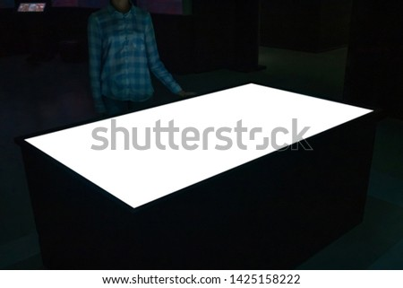 Mock up, copyspace, template, education, future and technology concept - woman looking at white blank interactive touchscreen display table kiosk in dark room of modern technology museum #1425158222