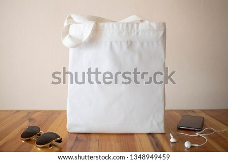 Mock up design bag. Blank white tote bag canvas fabric with sunglasses, smartphone and headphone on wooden table. Eco or reusable shopping bag. No plastic bag and ecology concept.
