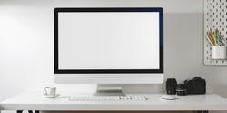Mock up desktop computer with camera and office supplies in modern office style on white desk