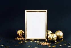 Mock up frame on dark background with Christmas decorations glitter snowflakes, baubles, bell and stars confetti. Invitation, card, paper. Place for text Trendy black and gold