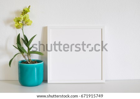 mock up frame photo with yellow orchid flower on white table in room