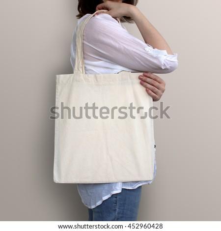 Mock-up. Girl is holding blank cotton tote bag. Handmade eco shopping bag for girls.