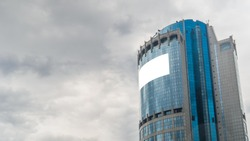 Mock up image - blank white billboard or large advertising display on tall building, glass skyscraper. Daylight, overcast. Consumerism, mockup, background, isolated white screen, copyspace concept