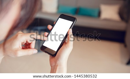 Mock up image of hand touching smartphone with blank white screen in home interior, living room, copy space.