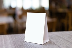 Mock up Label the blank menu frame in Bar restaurant. Stand for booklet with white sheet paper acrylic tent card on table wiht blurred background can inserting the text or picture.