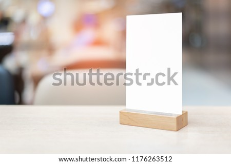 Mock up Label the blank menu frame in Bar restaurant ,Stand for booklets with white sheet on wooden table cafeteria blurred background
