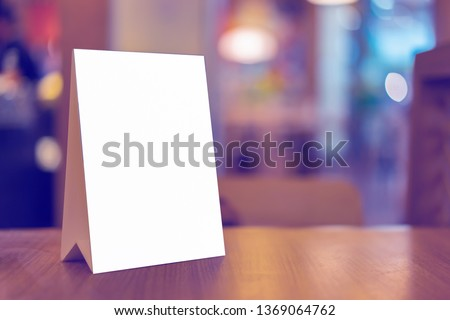 Mock up Label the blank menu frame in Bar restaurant ,Stand for booklets with white sheets paper acrylic tent card on wooden table cafeteria blurred background can inserting the text of the customer. #1369064762