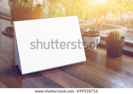 Mock up Label the blank menu frame in Bar restaurant ,Stand for booklets with white sheets paper acrylic tent card on wooden table cafeteria blurred background can inserting the text of the customer. #699928756
