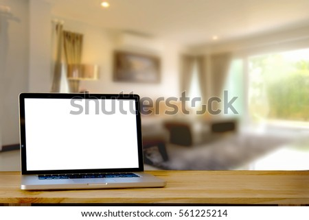 Mock up Laptop blank screen on wooden table in living room.