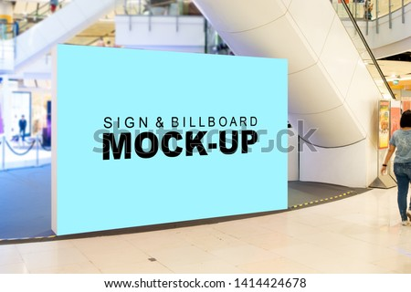 Mock up large blank billboard with clipping path placed on walkway in shopping mall and blurred people walking in background, empty space for advertising or information, advertising concept