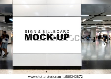 Mock up large blank horizontal billboard in metal frame with clipping path on the wall near walkway in airport terminal , blurred people walking, empty space for insert advertising or media