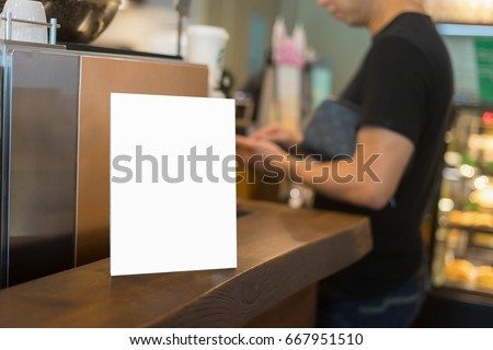Mock up Menu frame on Table in Bar restaurant or coffee shop ,Stand for booklets with white sheets of paper acrylic tent card on cafeteria ,barista preparing cup of coffee for customer in background.