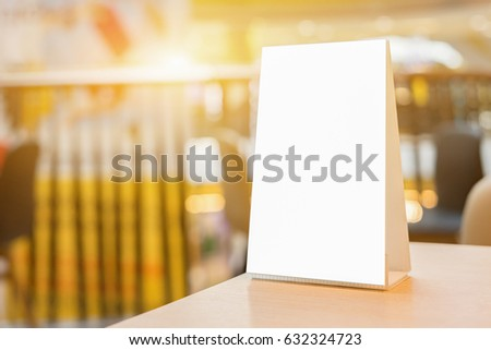 Mock up Menu frame on Table in Bar restaurant ,Stand for booklets with white sheets of paper acrylic tent card on cafeteria blurred background #632324723