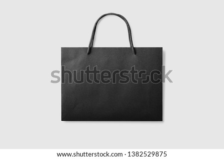 Mock up of a black paper shopping bag with handles on light grey background. High resolution.
