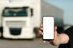 Mock up of a smartphone in a man's hand. Against the backdrop of trucks. Logistics concept