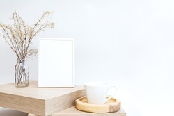 Mock up of a white photo frame in a minimalistic interior with a bouquet of pampas grass in a glass vase against a white wall background