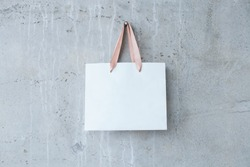 Mock-up of blank craft package, mockup of white paper shopping bag with handles on the concrete background.