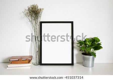 mock up of blank photo frame with book and plant pot. Minimal home decor