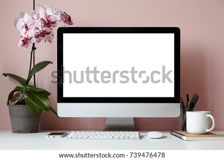 Mock up of creative desktop of female designer with nobody around: modern electronic gadgets, mouse, stationery accessories, notebook, cup and decorative plant against blank pink wall background #739476478