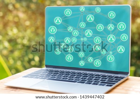 Mock-up of laptop screen with global structure networking social network diagram which contain people icons connected to each other on desk outdoor with green tree background. Data connection concept. #1439447402