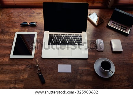 Mock up of modern freelance desktop with accessories and distance work tools, blank screen laptop computer and digital tablet, sunglasses, cup of coffee, touch pad and hard drive, business workspace