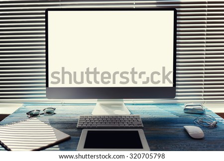 Mock up of office or home desktop with accessories and work tools, blank screen pc computer, keyboard with mouse, sunglasses, digital tablet, empty touch pad and headphones, modern hipster workspace