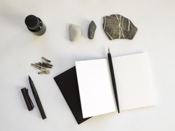 Mock up of opened white notebook for sketch, artwork or calligraphy. Desk work in white with sketchbooks, pens, black ink, quill and calligraphy utensils. Blank template with white pages A5