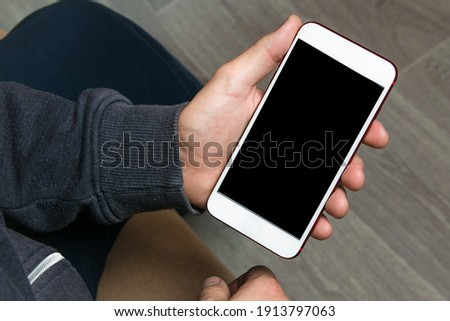Mock up of smartphone held by the hands of a man. Template for corporate material Stockfoto ©