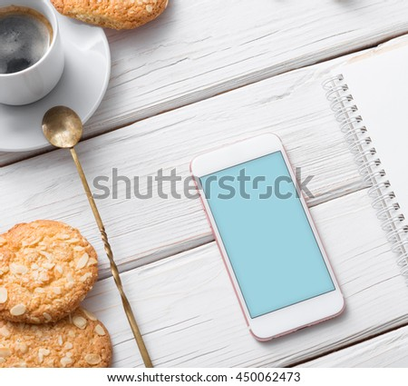 Mock up of white smart phone on a cafe desktop among cookies with coffee cup. Clipping path included. #450062473