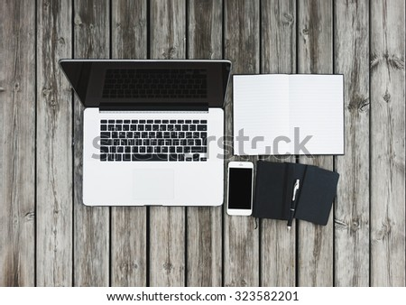 Mock up of workspace on wooden desk with laptop and white smartphone with blank screen, open notebook