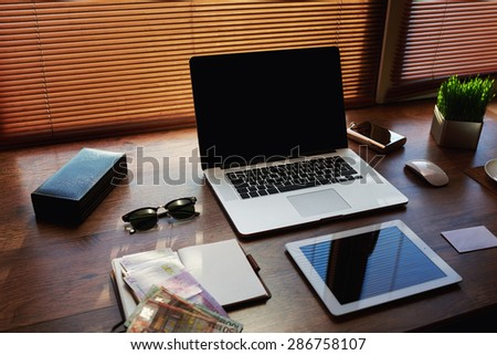 Mock up of workspace with laptop computer and digital tablet, electronic business and distance work concept, successful businessman or entrepreneur wooden table with style accessories and euro bills