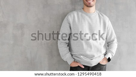 Mock up of young man body in empty sweatshirt isolated on textured gray wall background. No face photo