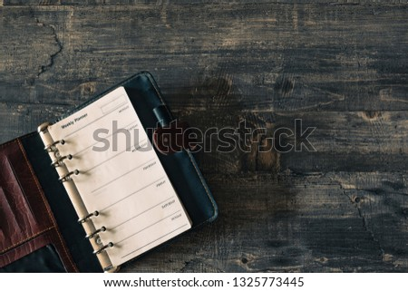 Mock-up Old notebook weekly planner on dark wooden table desk. Flat lay templat. Top view layout #1325773445