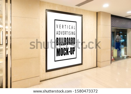 Mock up perspective vertical blank vertical billboard with clipping path on wooden wall with black frame of duty shop at airport, empty space for advertising or information