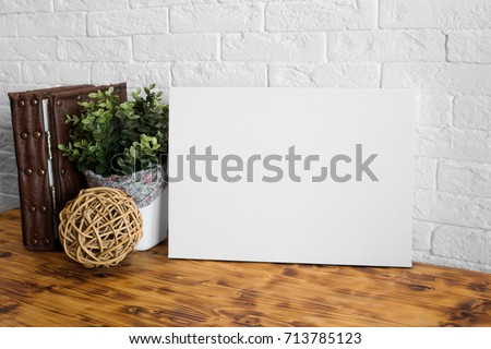 Mock up poster in the interior. Blank canvas frame. Wooden table and white brick wall on background. #713785123