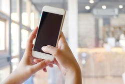 Mock up smartphone blank screen in female hands in blurred office interior background.