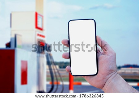 Mock up smartphone in hand closeup on the background of a gas station. Payment refueling online Сток-фото ©