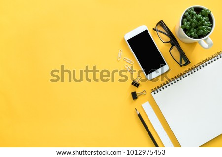 Mock up smartphone with office accessories on yellow background #1012975453