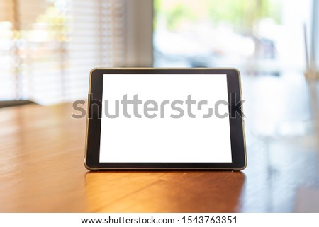 Mock up tablet like iPad stand on the wooden desk in office background with white screen clipping path