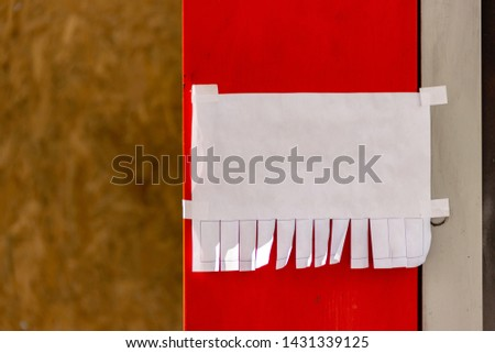Mock up template. Street paper ad or announcement with tear-off stripes with phone number. Blank design. Natural sunny lighting. Red painted surface. White adhesive plaster on edges. Copyspace mockup