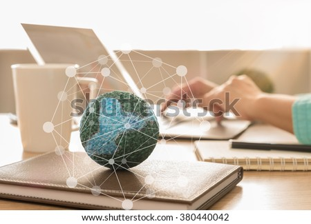 mock up the globe with digital social media network on notebook at office background. #380440042