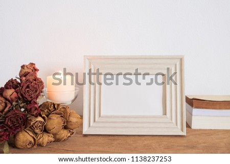Mock up vintage frame photo with candle light and dried rose flowers bouquet on table