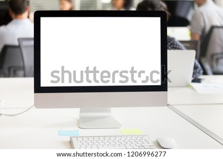 Mock up white computer screen on desk at office background, mockup blank display on table at workplace, empty device monitor with copyspace and icons for business work and software applications usage #1206996277