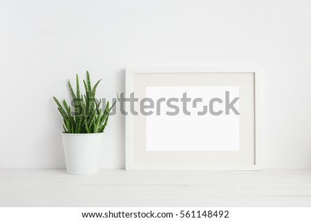 Mock up white frame and aloe vera plant on book shelf or desk. White colors.