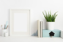 Mock up white frame, books, office supplies and houseplant on well arranged desk. Bright colors.